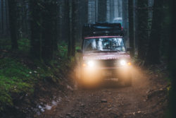 1991 red Range Rover Classic driving at night in the woods