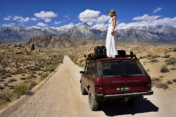 Woman in a wedding dress standing on a red 1991 Range Rover Classic SUV